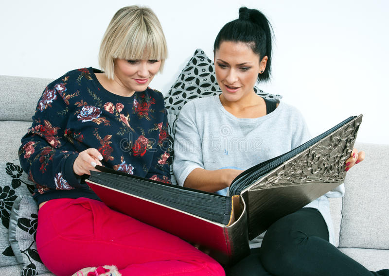 Two attractive woman friends with photo album royalty free stock images