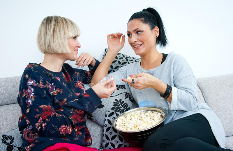 Two attractive woman friends with popcorn talking royalty free stock image