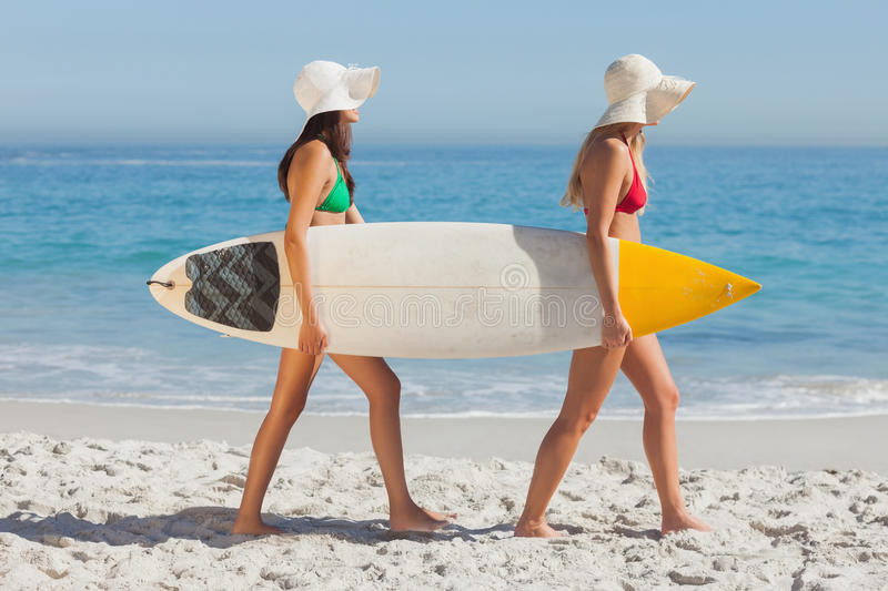 Two attractive women in bikinis holding a surfboard. On the beach royalty free stock photography