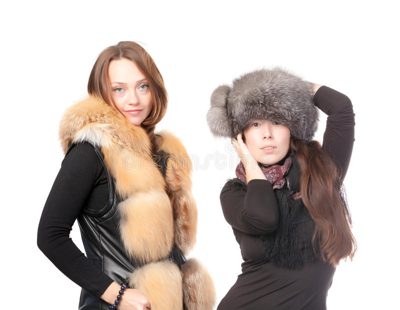 Two attractive women dressed for winter. Posing together on a white background in fur trimmed garments stock photos