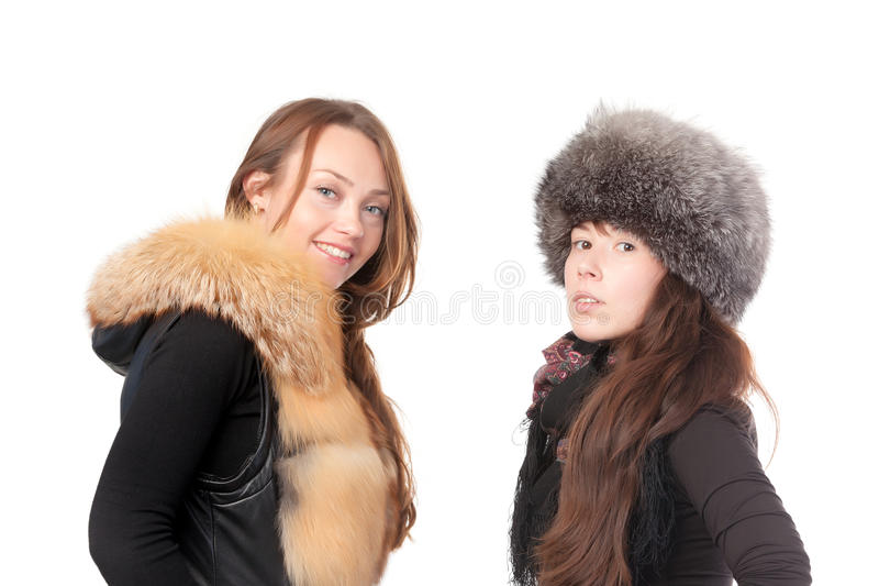 Two attractive women dressed for winter. Posing together on a white background in fur trimmed garments royalty free stock image