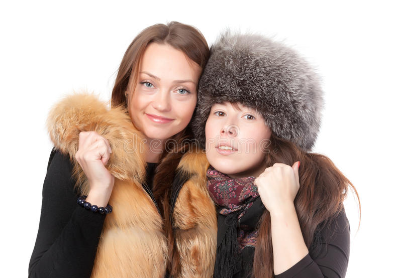 Two attractive women dressed for winter. Posing together on a white background in fur trimmed garments royalty free stock photos