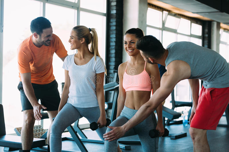 Two attractive women exercising with personal trainers royalty free stock photo