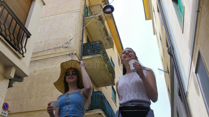 Two attractive women walk on the city in the narrow street. Mid shot royalty free stock image