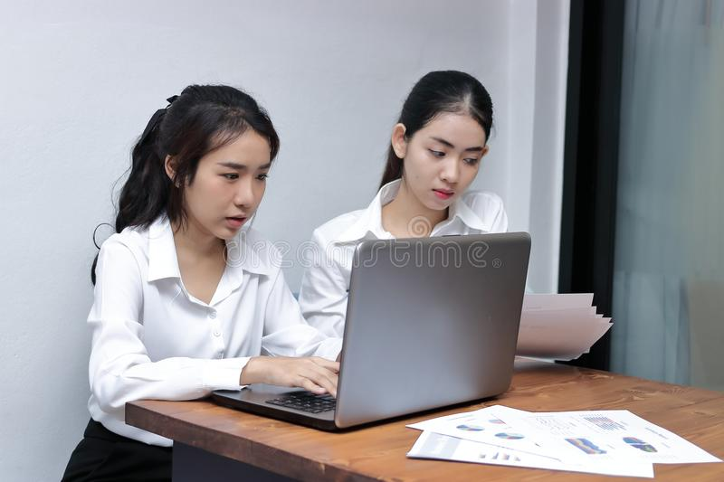 Two attractive young Asian businesswoman using laptop together in modern office. Team work business concept. stock photo