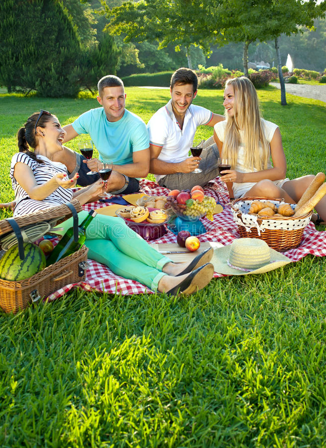 Two couples picnicking in a park stock images