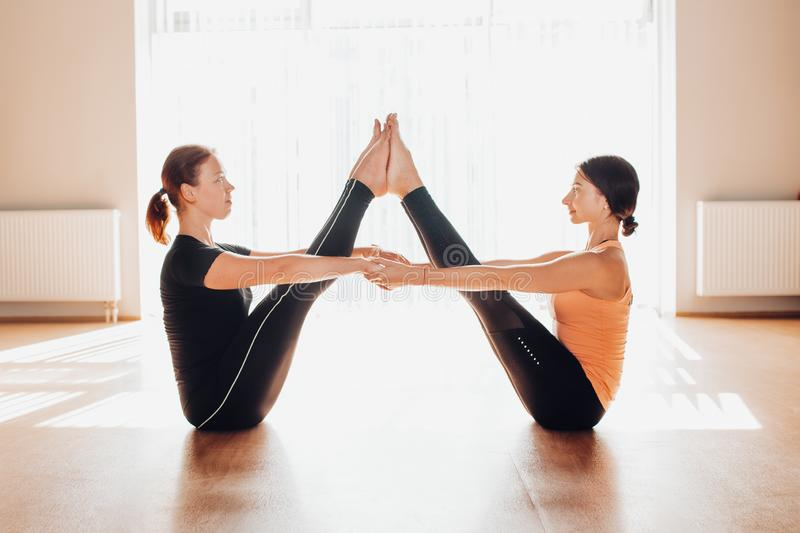 Two attractive young women balancing and practicing yoga in a light studio. Well being, wellness concept. One of the woman is plus. Two attractive young women royalty free stock photo