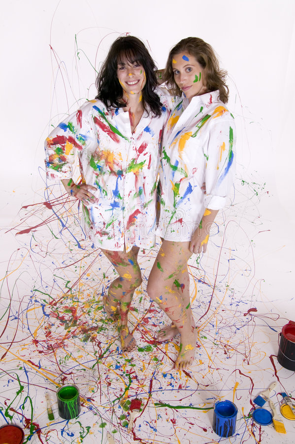 Two attractive young women covered in colorful paint royalty free stock images