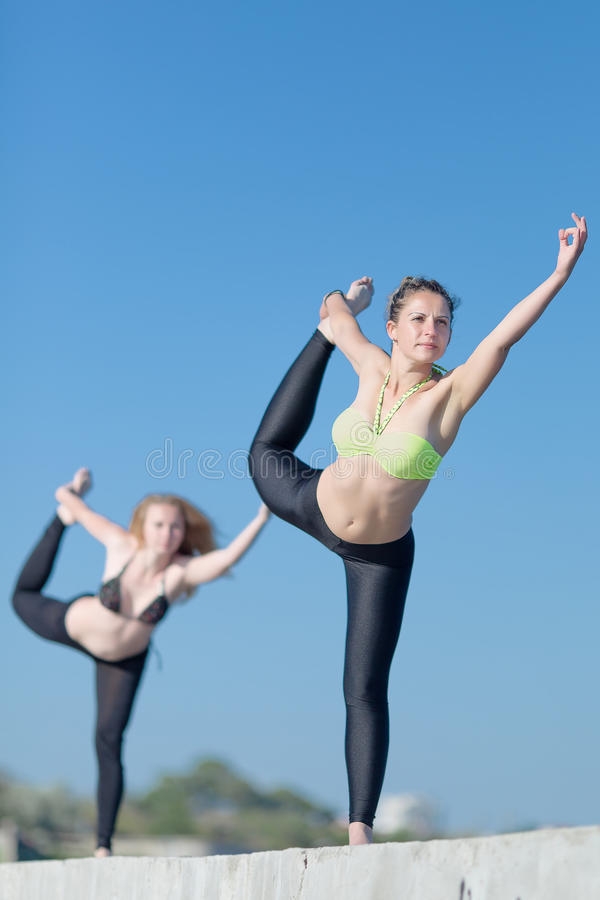 Two attractive young women exercising outdoors. Girls doing yoga outdoors. Two attractive young women exercising on open air royalty free stock image