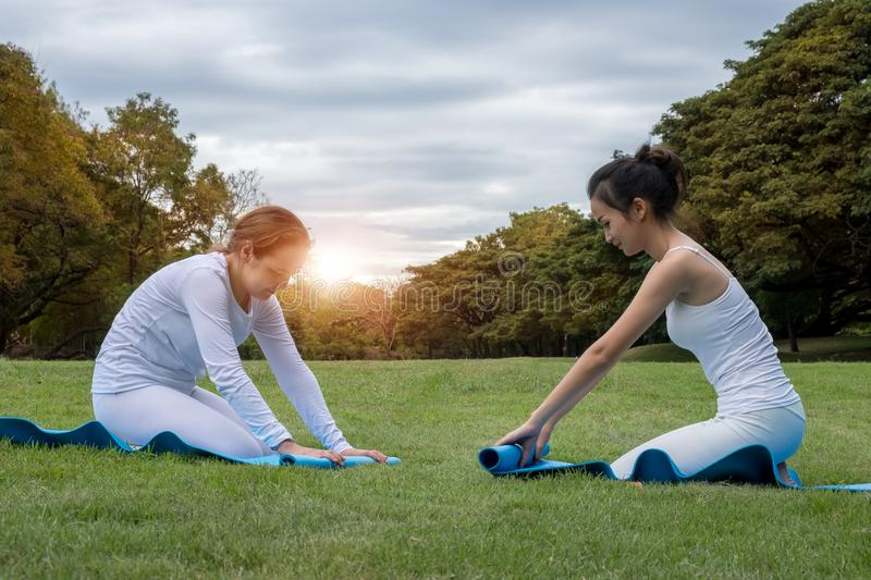 Two attractive young women folding blue yoga or fitness mat after working out at the garden. Healthy life, keep fit concepts. royalty free stock photo