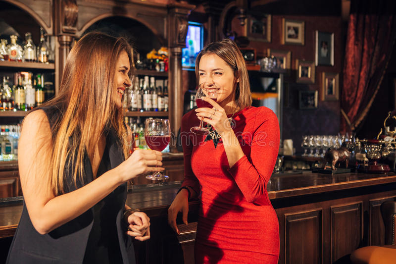 Two attractive young women meeting up in a pub for glass of red wine sitting at counter smiling each other. Two attractive young women meeting up in a pub for a royalty free stock image