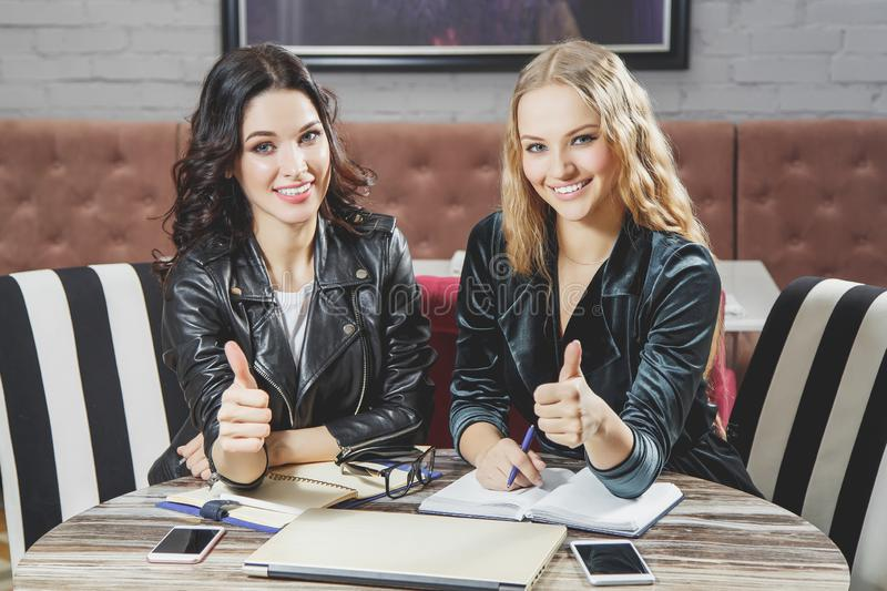 Two attractive young women showing thumb up. Business meeting. stock photography