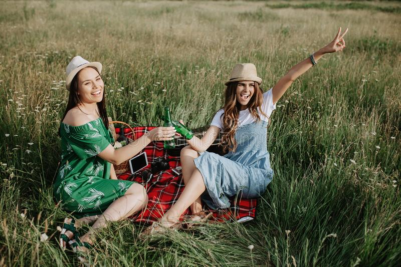 Two attractive young women sitting down on the picnic blanket and have fun. Beer and sandwiches. stock images