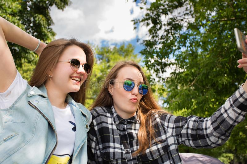 Two beautiful woman takes selfie by smart phone in the park. Two attractive young women or student in sunglasses resting in the park and taking a selfie with a stock images