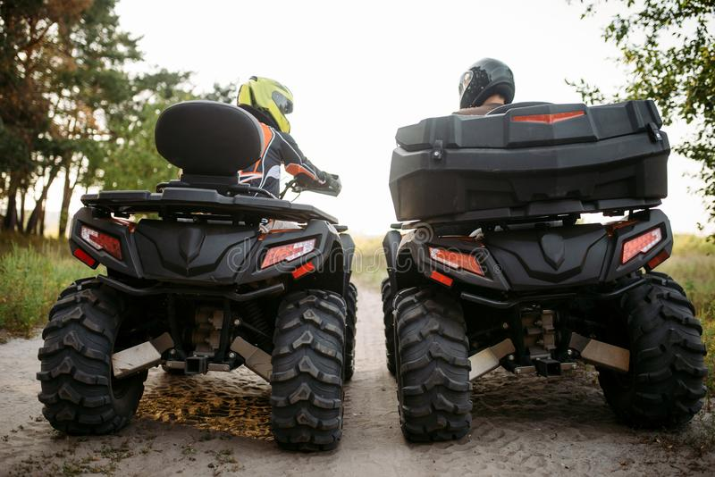 Two atv riders in helmets, back view, quad bike royalty free stock photos