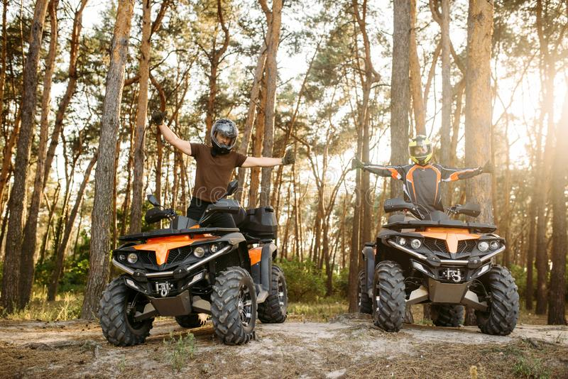 Two atv riders in helmets raise their hands up royalty free stock photo