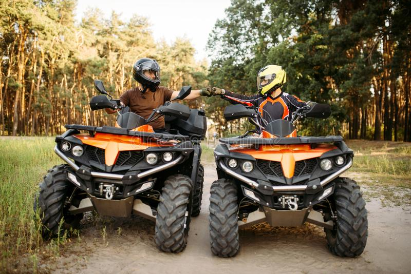 Two atv riders hits fists for good luck, back view royalty free stock photos