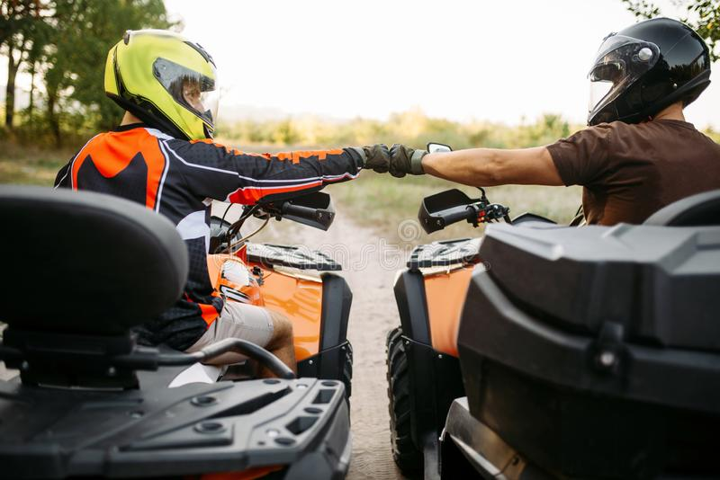 Two atv riders hits fists for good luck, back view royalty free stock photography
