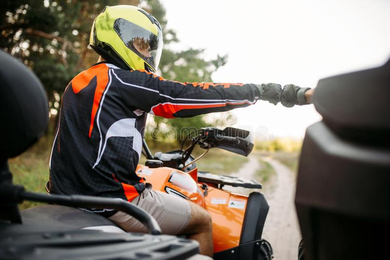 Two atv riders hits fists for good luck, back view stock photos