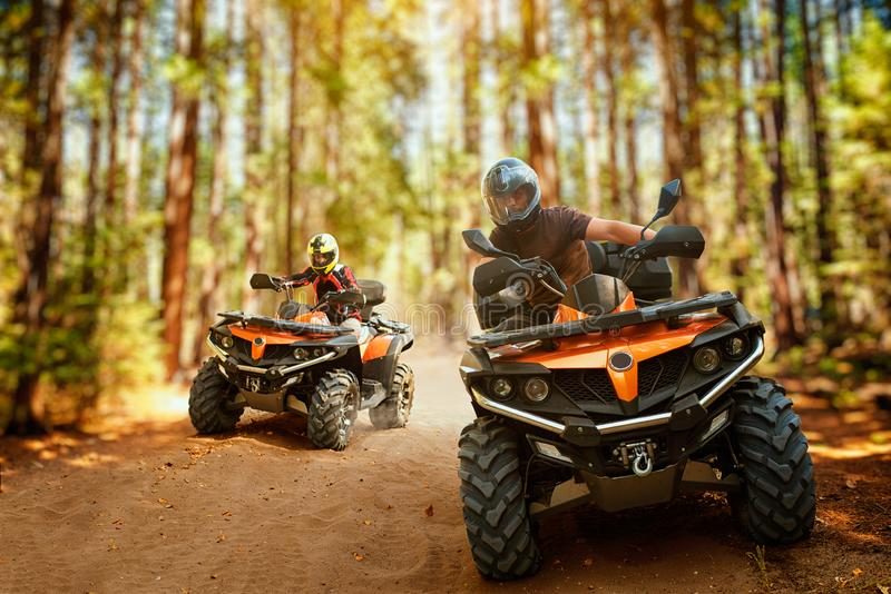 Two atv riders, speed race in forest, front view royalty free stock photos
