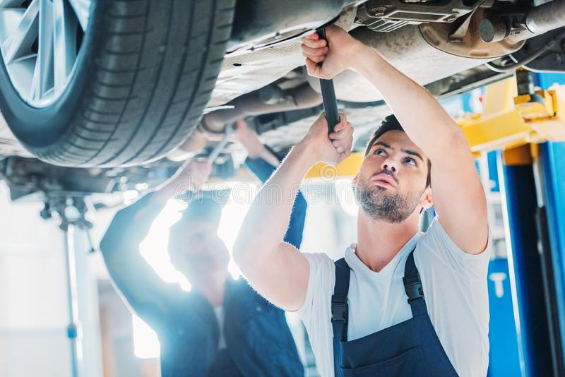 Automechanics working on car. Two automechanics working on a car in a repair workshop royalty free stock photo