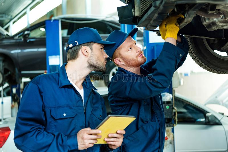 Automechanics working on car. Two automechanics working on a lifted up car in a repair workshop royalty free stock images