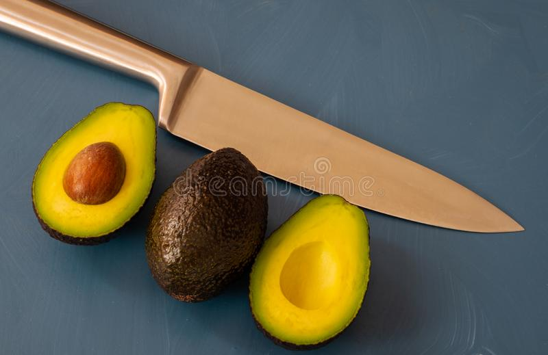 Two avocados on blue background with knife. Cut 2 slices stock images
