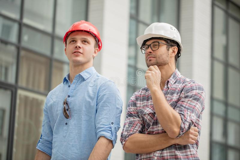 Two awesome builders thinking about the design of construction. Close up low angle portrait royalty free stock images