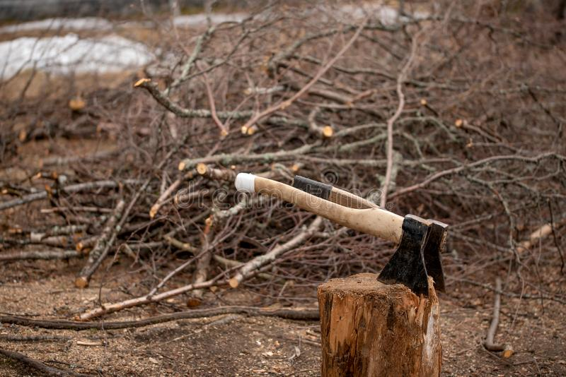 Two axes in a stub for splitting of firewood in the yard. Of a country house stock photo
