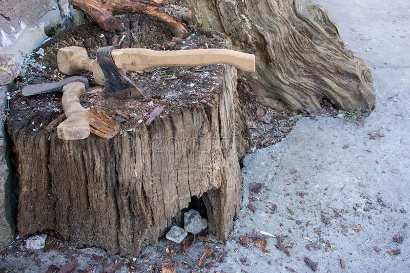Two axes in weathered stump tree. Danger concept. Rusty tool background. Wooden axe. Cold weapon concept. Firewood concept. Backyard background royalty free stock photos