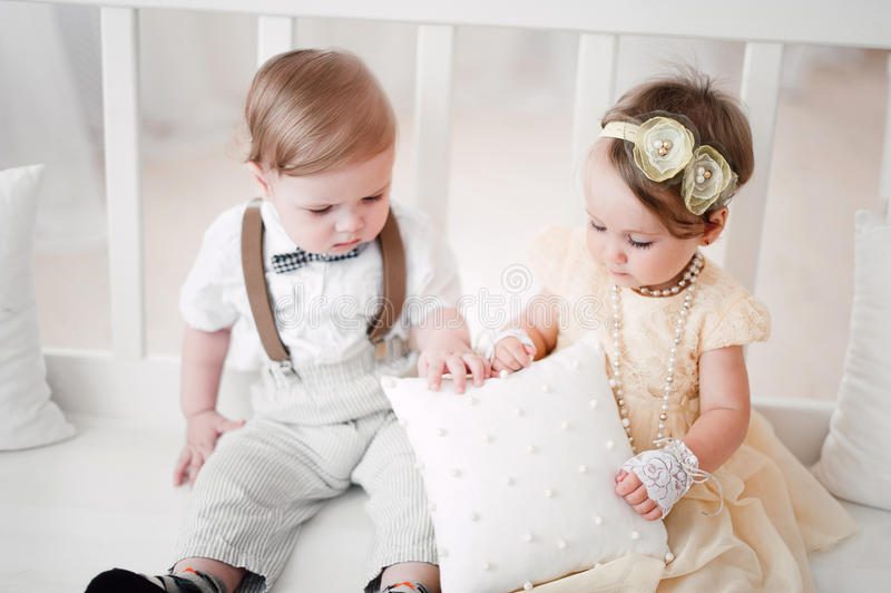 Two babies wedding - boy and girl dressed as bride and groom. Two babies - boy and girl dressed as bride and groom stock photos