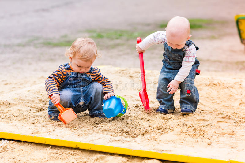 Two baby boys playing with sand royalty free stock photography