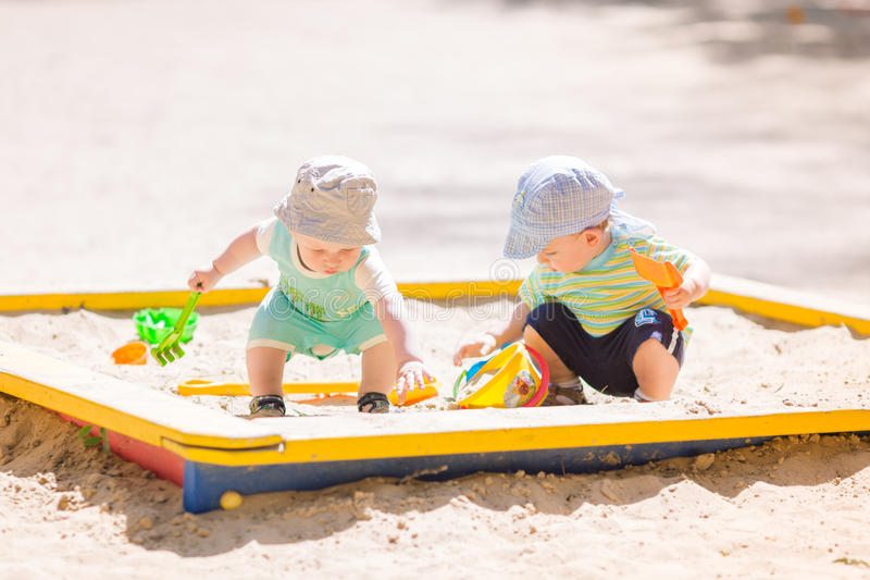 Two baby boys playing with sand royalty free stock images