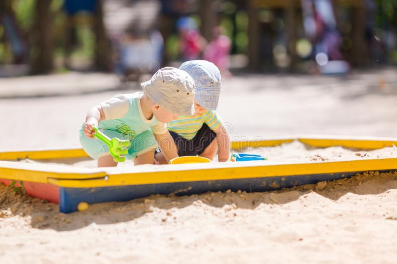 Two baby boys playing with sand royalty free stock photo