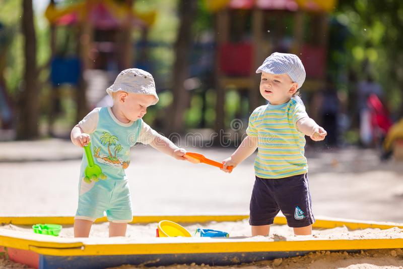 Two baby boys playing with sand royalty free stock photos