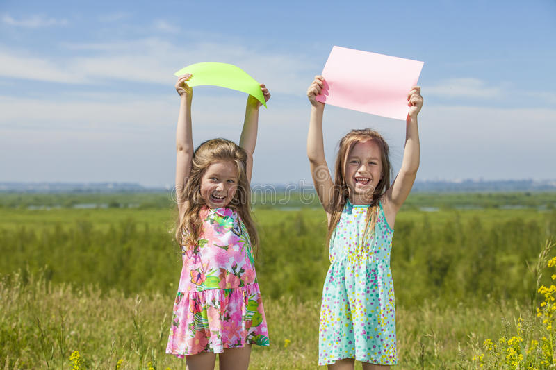 Two baby girls in summer dresses on the nature of holding the co. Lored sheets of paper. Summer, sun, green, meadow stock photo