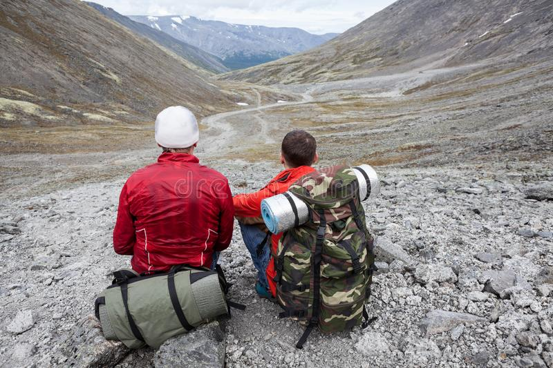 Two backpackers sitting on stone and looking at distance, the only one way through the valley royalty free stock photos