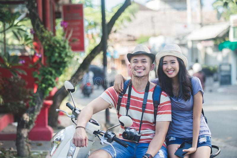 Two backpackers with summer hat smiling while sitting on motorbi. Portrait of two backpackers with summer hat smiling while sitting on motorbike resting for a stock photos