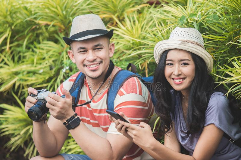 Two backpackers with summer hat smiling to camera. Portrait of two backpackers with summer hat smiling to camera while sitting on the side of the road royalty free stock images