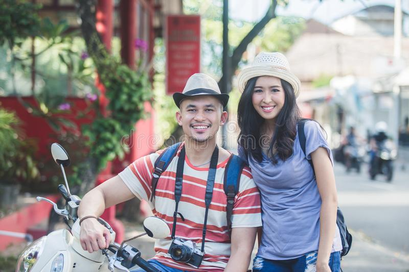 Two backpackers with summer hat smiling to camera while sitting royalty free stock image