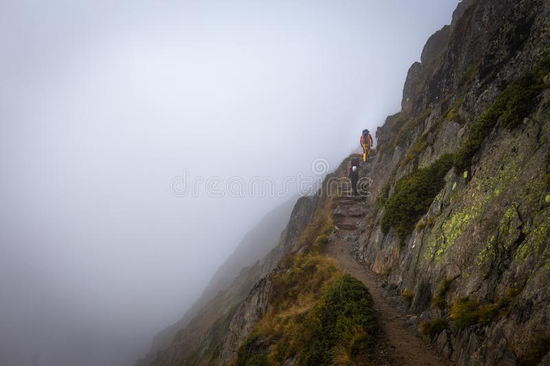 Two backpackers walking mountain cliff trail. Two backpackers mountaineers walking hiking ascending mountain cliff lane trail path covered fog stone stairs steps stock photos