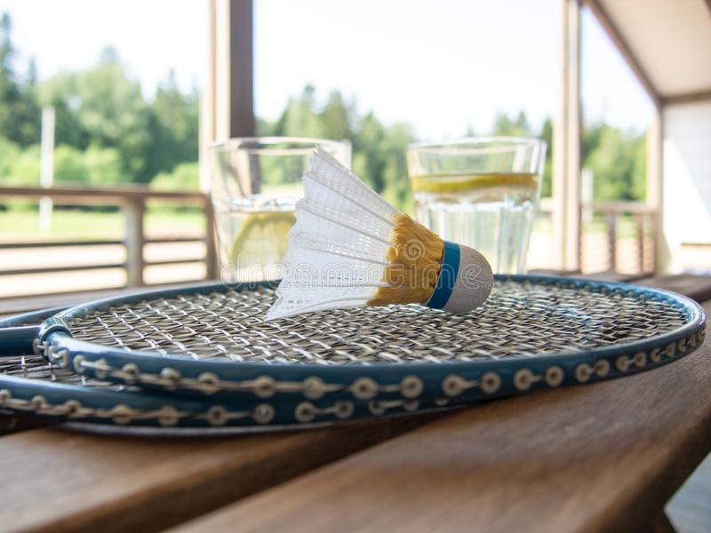 Two badminton rackets and shuttlecock in the foreground on a wooden table. Two glasses with a refreshing lemonade with a slice of. Two badminton rackets and stock image