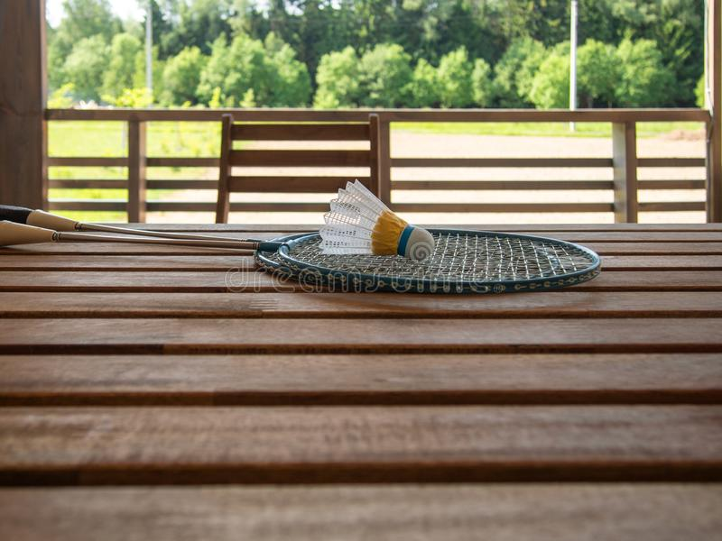 Two badminton rackets and shuttlecock lie on a wooden table on the terrace of a country house. Lush green foliage in the. Background. Wooden country furniture stock photos
