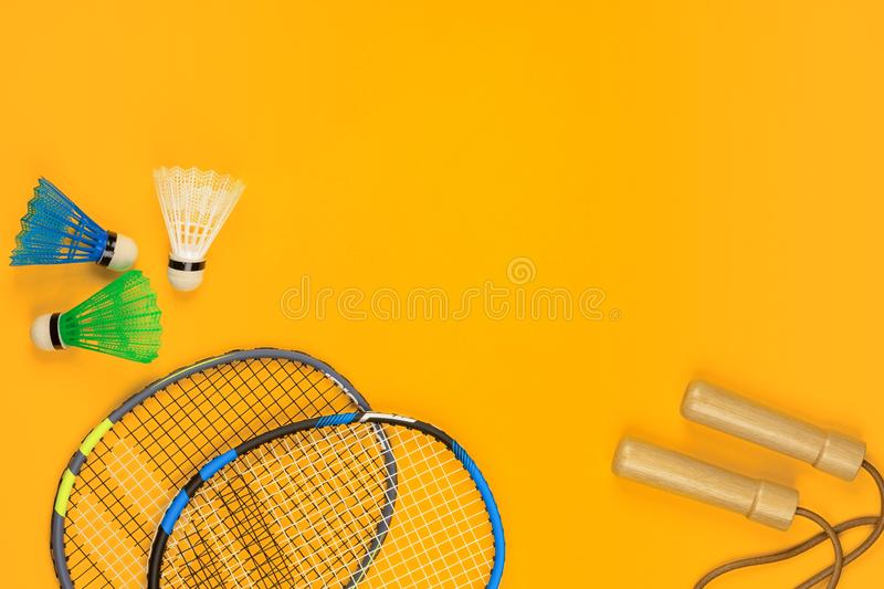 Two badminton rackets and two shuttlecocks next to a jump rope on yellow background. Shot from above stock image