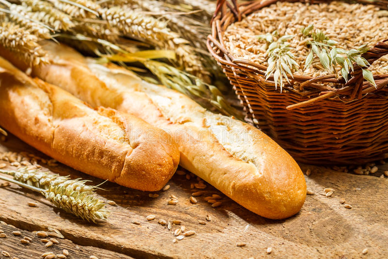 Two baguettes and a basket of grain stock photography
