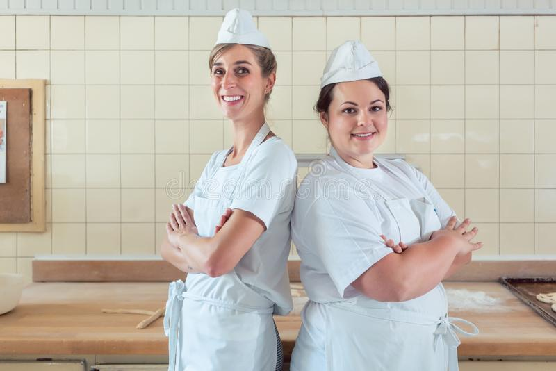 Two baker women standing proud in their bakery royalty free stock images