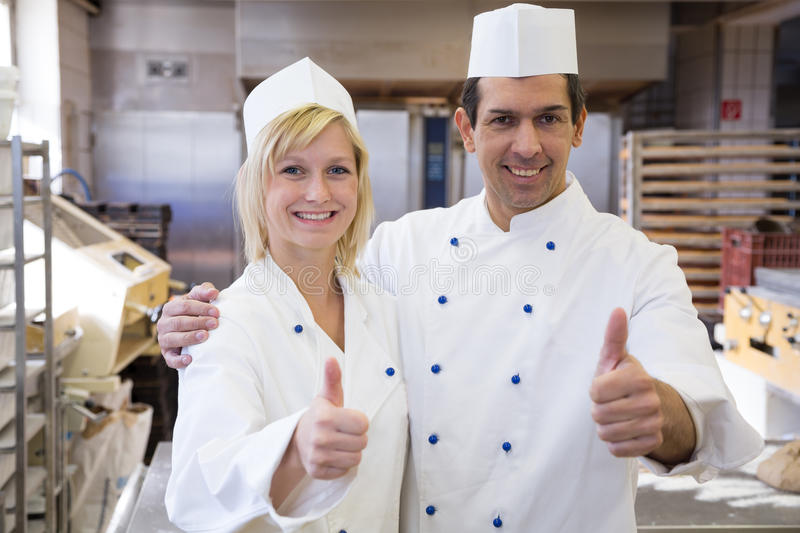Two bakers showing thumbs up in bakeshop stock photos