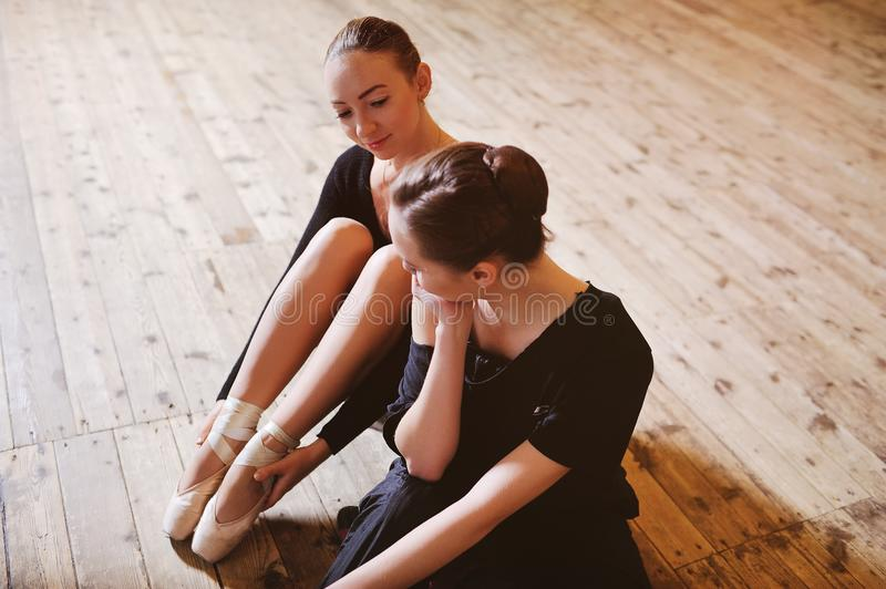 Two ballerinas talking and smiling sitting on a wooden floor royalty free stock photography
