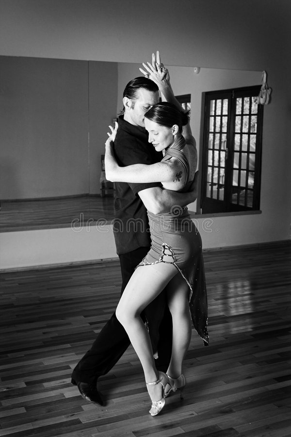 Two ballroom dancers practicing. A young adult couple dancing and practicing ballroom dancing together in a studio - Focus on woman, Black and white - high key royalty free stock photo