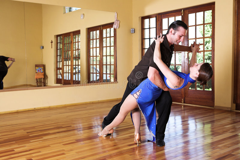 Two ballroom dancers practicing in their studio. A young adult couple dancing and practicing ballroom dancing together in a studio - Focus on woman royalty free stock image